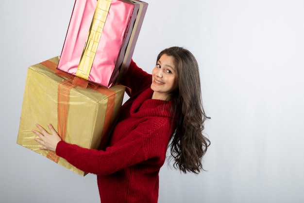 Cute woman in red sweater holding christmas presents .