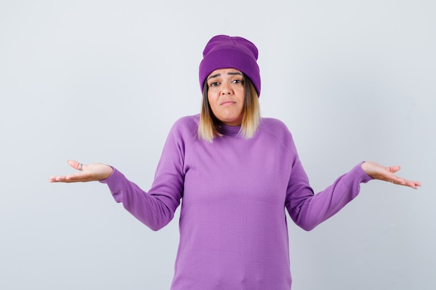 Cute woman showing helpless gesture in sweater, beanie and looking confused , front view.