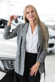 Cute woman showing at keys of the car and looking away