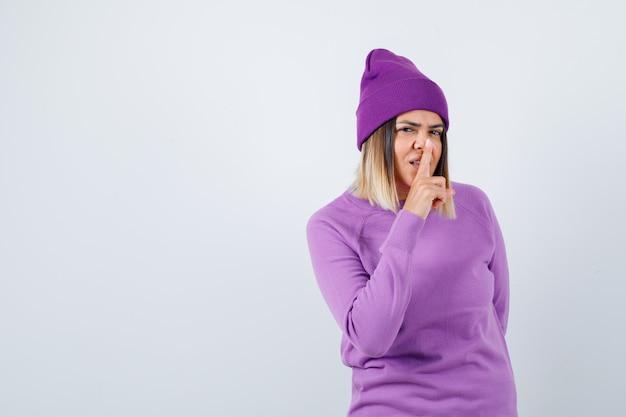 セーター、ビーニーで沈黙のジェスチャーを示し、賢明に見える、正面図のかわいい女性。