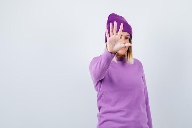 セーター、ビーニーで停止ジェスチャーを示し、毅然とした表情でかわいい女性。正面図。