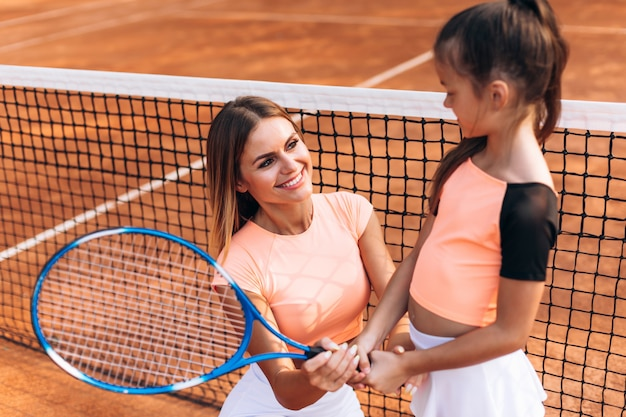 Cute woman shows girl how to hold racket