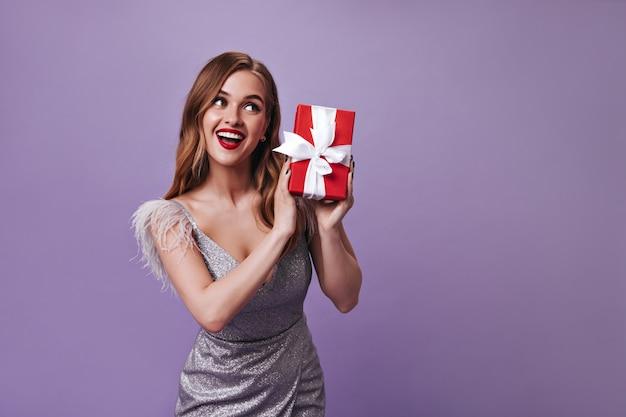 Cute woman in silver dress holding gift on purple wall