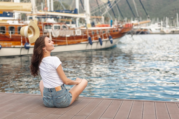 Cute woman sitting on the shore of a port