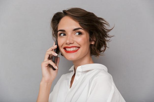 かわいい女性の笑顔と携帯電話で話す、灰色の壁に隔離