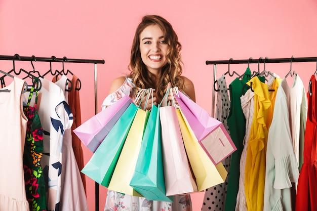 Милая женщина стоит в магазине возле вешалки и держит красочные сумки для покупок, изолированные на розовом