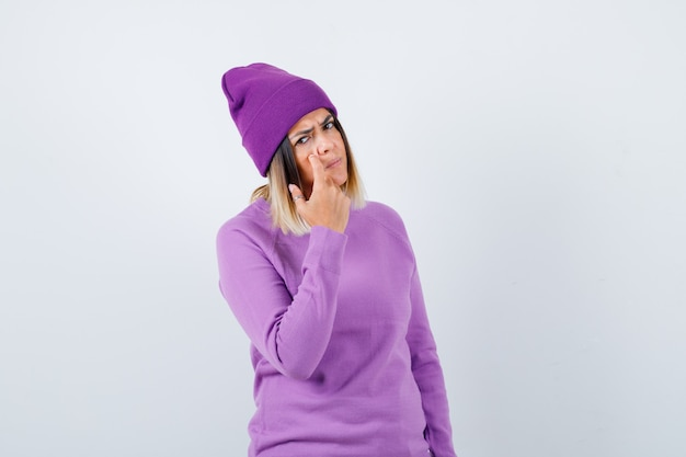 Cute woman in sweater, beanie pointing at her eyelid and looking upset , front view.