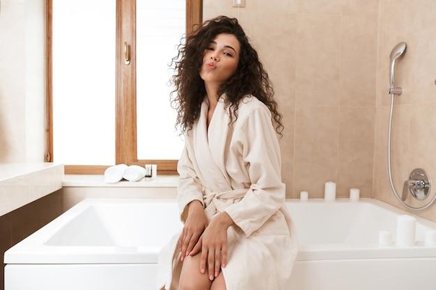 Милая женщина заботится о своей коже в ванной комнате.