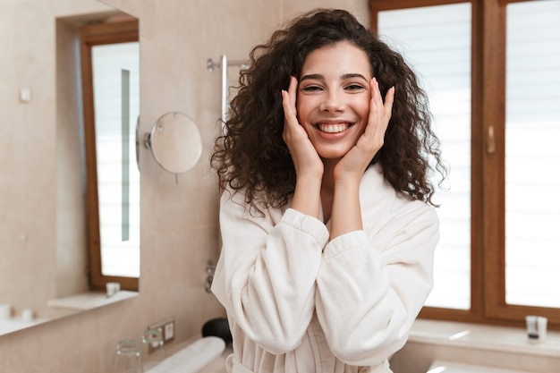 귀여운 여자는 화장실에서 그녀의 피부를 돌봐.