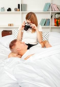 Cute woman taking a photo of her boyfriend in bed