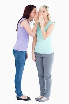 Cute woman telling friend a secret