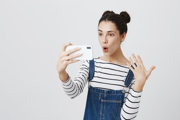 Симпатичная женщина в видеочате через смартфон, запись видеоблога на мобильный телефон