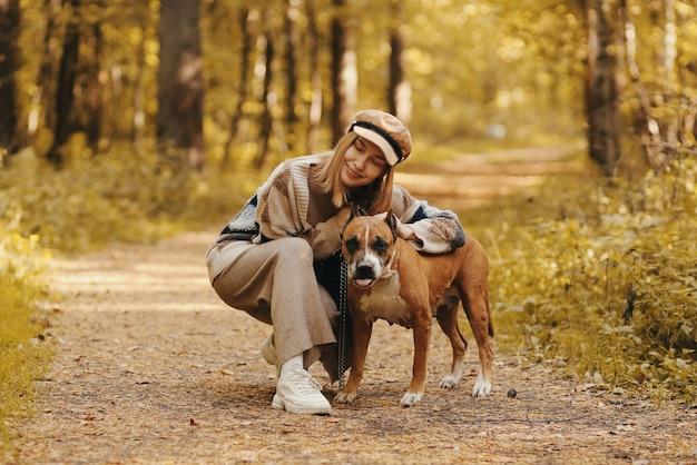 秋の森で彼女の犬と一緒に歩いているかわいい女性
