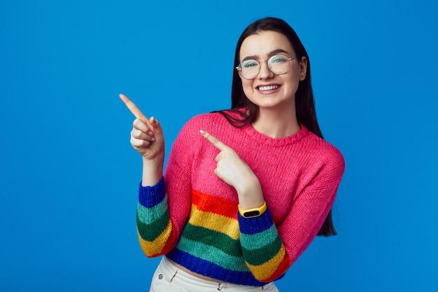 Симпатичная женщина в стильном радужном свитере, указывая обеими руками слева
