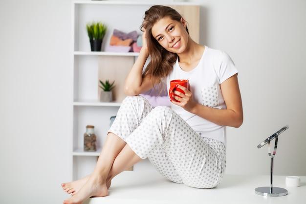 Милая женщина с красивой улыбкой в новой пижаме готовится ко сну