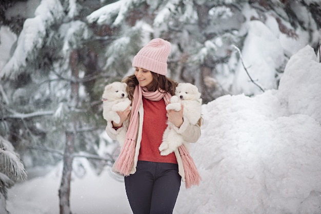 冬の森のふわふわの白い子犬とかわいい女性
