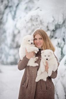 겨울 숲에서 두 개의 솜털 흰 개를 가진 귀여운 여자