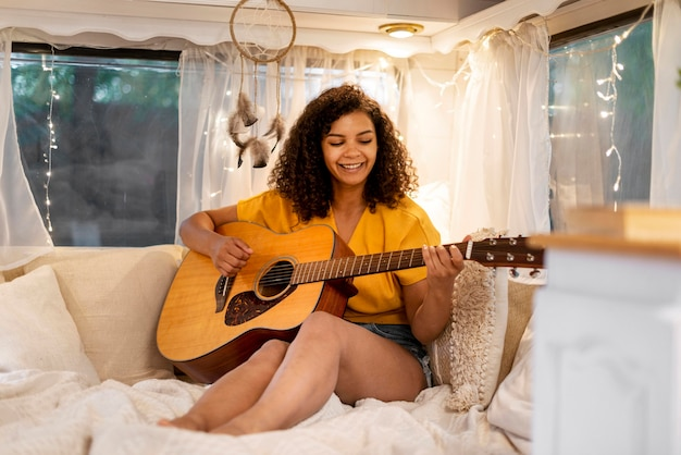 Cute woman with curly hair playing guitar