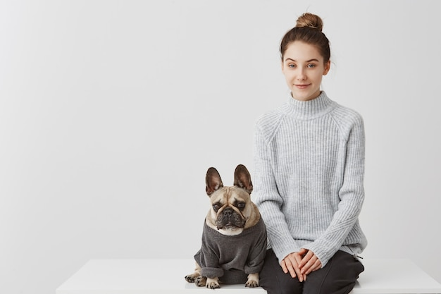 Cute woman with fashion hairstyle and her puppy french bulldog dressed in jumper. female model sitting on table with dog over white wall. friendship concept, copy space