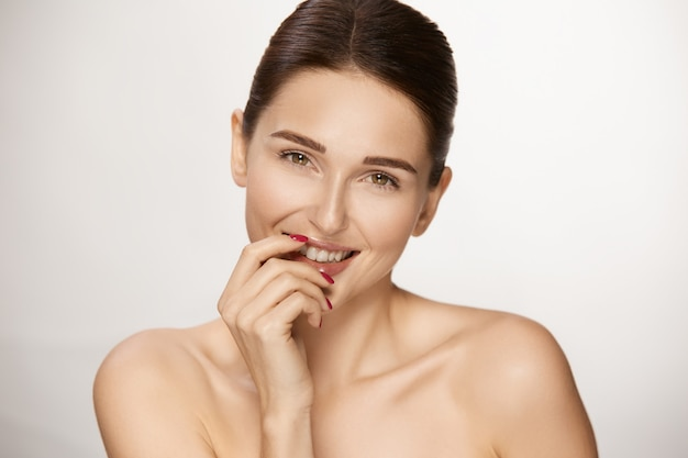 Cute woman with fresh skin smiling and holding arm near mouth, young woman with light daily make-up and perfect smile