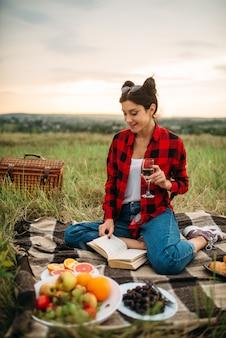 ワインのグラスを持つかわいい女性は、草原でピクニック、本を読みます。ロマンチックなジャンケット、幸せな休日