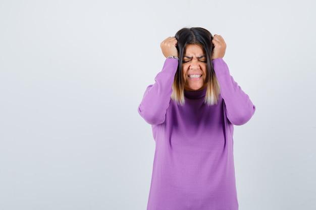 紫色のセーターを着て頭に手を当ててイライラして見えるかわいい女性。正面図。