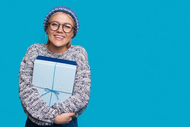 모자와 금발 머리를 가진 귀여운 여자는 뭔가 광고하는 동안 여유 공간이있는 파란색 벽에 선물을 포용하고 있습니다.