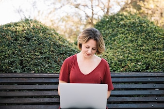 Cute woman with laptop in park