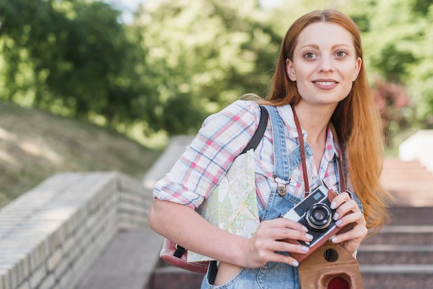 Cute woman with old camera smiling