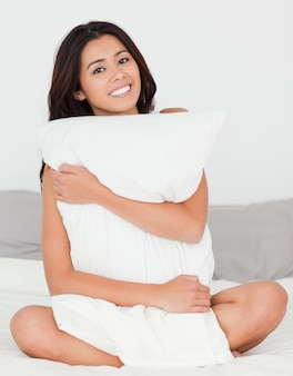Cute woman with pillow sitting on her bed smiling into camera