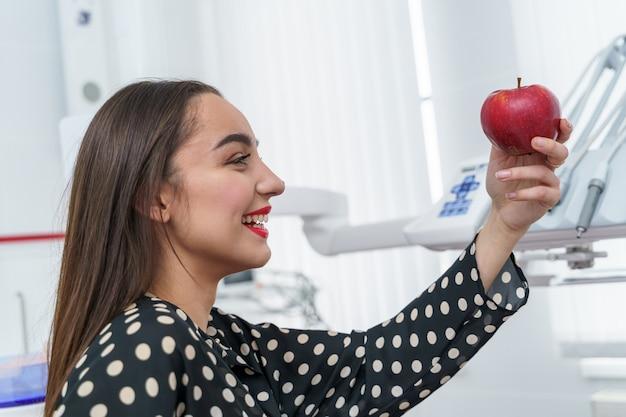 Милая женщина с красными губами. пациент в кабинете стоматолога. женщина с яблоком.