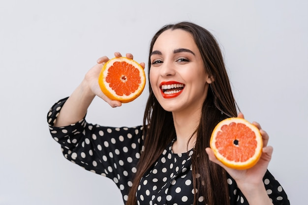 Cute woman with red lips. woman holding citrus fruit halves in hands showing to the camera. facial expressions.