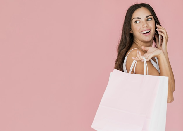 Cute woman with shopping bags looking back