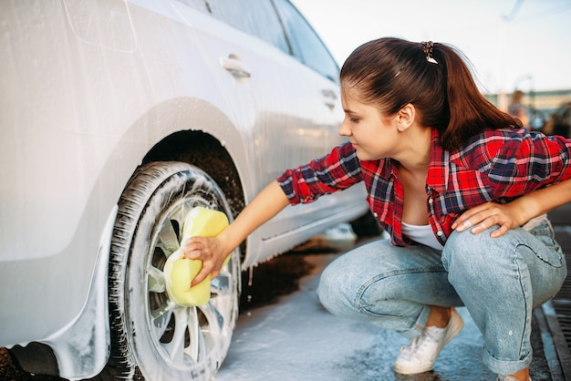 Cute woman with sponge scrubbing vehicle wheel with foam, car wash. lady on self-service automobile washing. outdoor carwash at summer day