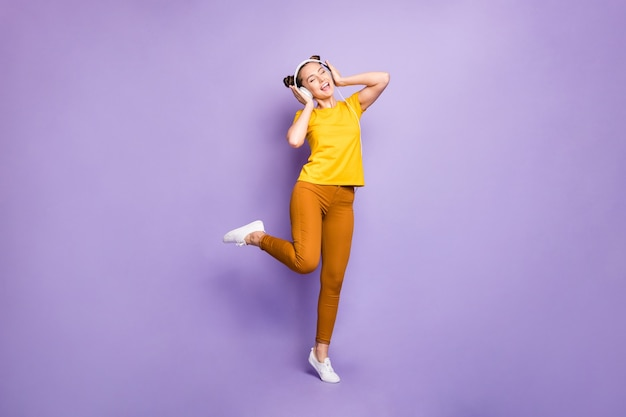 Cute woman with topknots posing against the purple wall