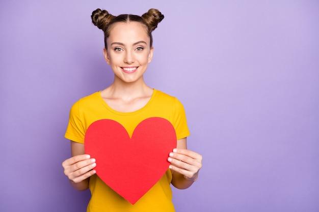Милая женщина с узлами позирует на фиолетовой стене