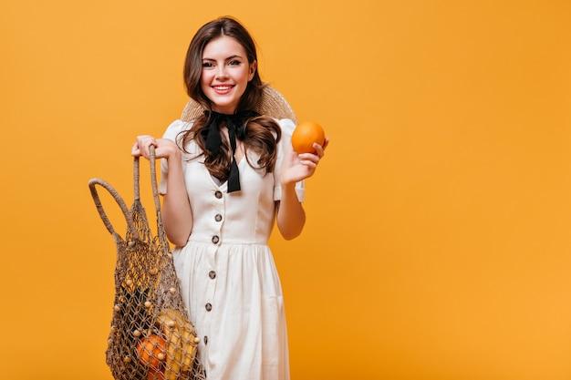 La donna carina con i capelli ondulati tiene la borsa arancione ed eco. ragazza in abito bianco e cappello esamina la macchina fotografica su sfondo arancione.