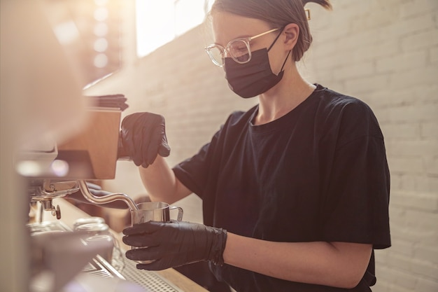 Cute woman working with coffee machine in cafeteria