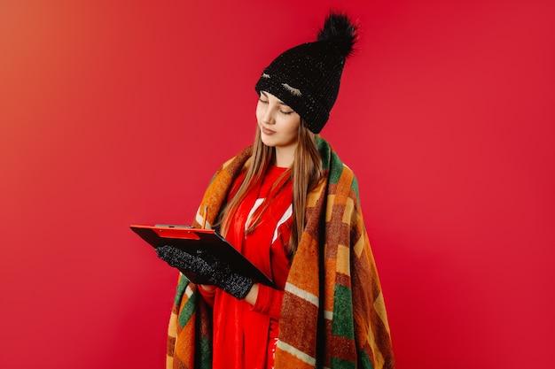 Милая женщина пишет в теплой шапке и укутывается в одеяло