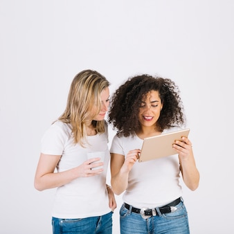 Cute women browsing tablet together