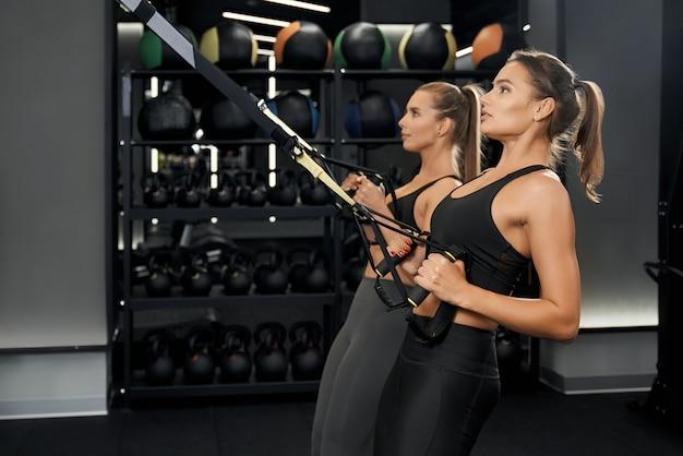 체육관에서 trx 시스템으로 운동을 하 고 귀여운 여자