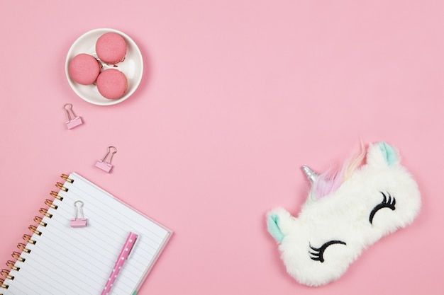 Cute women's or girls things, sleep mask, macarons, notepad, pen, clamps on pink background