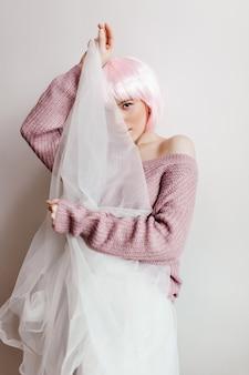 白い布の後ろに顔を隠すピンクの髪のかわいい素敵な女の子。明るい壁にふざけてポーズをとる光沢のあるかつらの華やかな女性モデル。