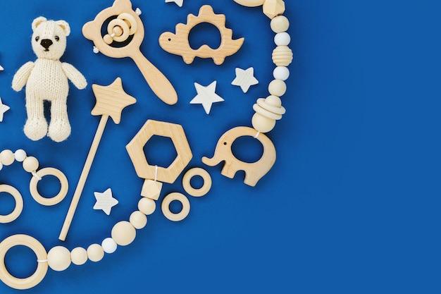 Cute wooden baby toys on blue background.