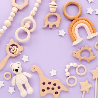 Cute wooden baby toys on light-blue background. knitted bear, rainbow, dinosaur toy, beads and stars. eco accessories,  beanbag and teethers for newborn. flat lay, top view