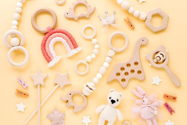 노란색 바탕에 귀여운 나무 아기 장난감입니다. 니트 곰, 무지개, 공룡 장난감, 구슬 및 별. 신생아를 위한 에코 액세서리, 빈백 및 치발기. 평평한 평지, 평면도