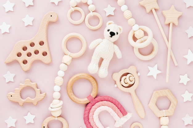 Cute wooden baby toys on pink background. knitted bear, rainbow, dinosaur toy, beads and stars.