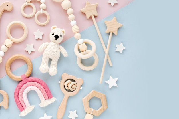 Cute wooden baby toys on pink and light-blue background.