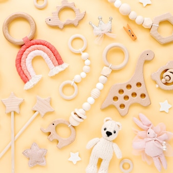 Cute wooden baby toys on yellow background. knitted bear, rainbow, dinosaur toy, beads and stars. eco accessories,  beanbag and teethers for newborn. flat lay, top view