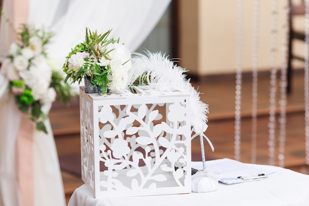 A cute wooden box with a carving for gifts on the table with a white tablecloth on the background of the arches decorated with tulle and flowers